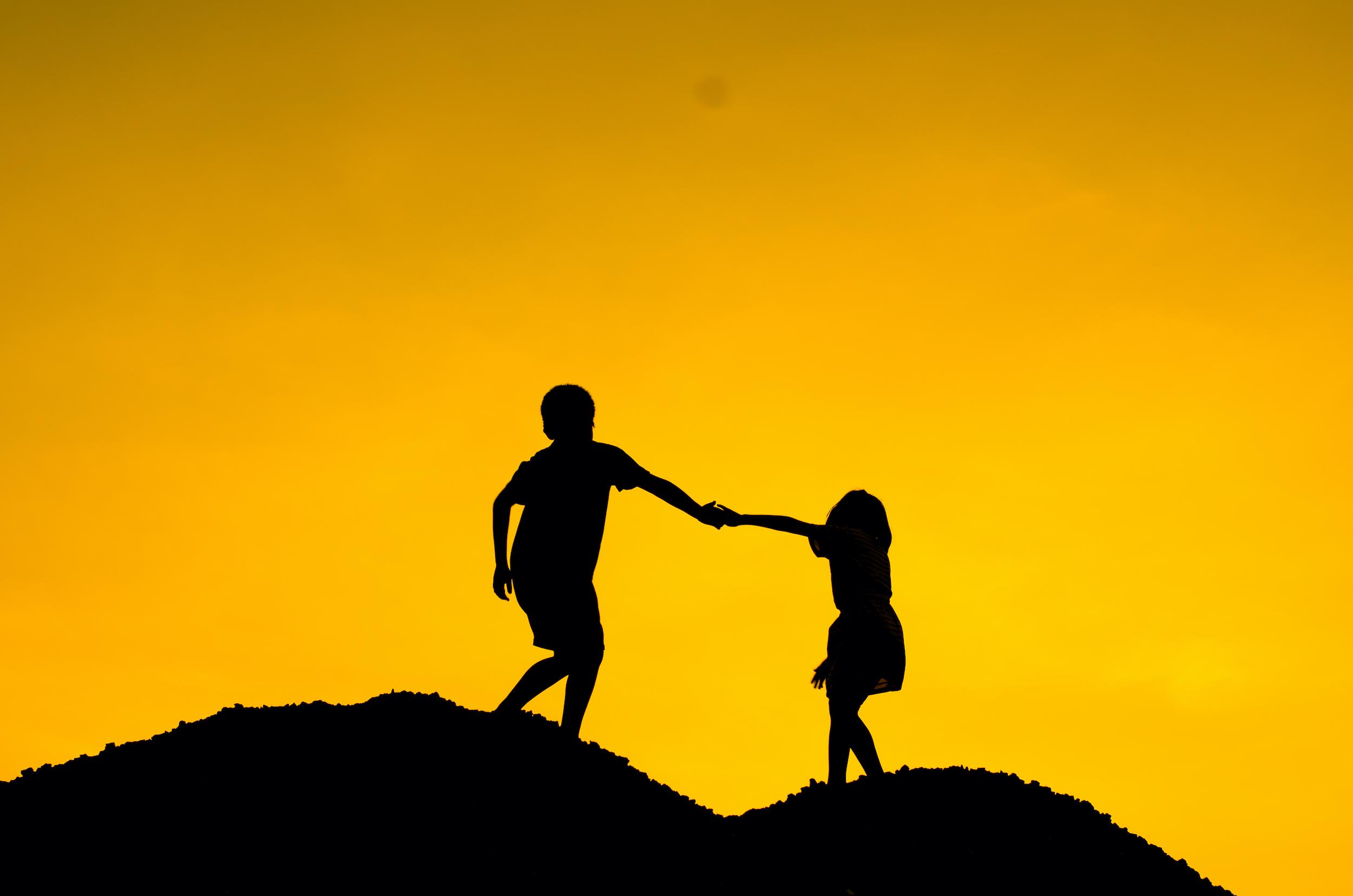 Boy holding girl hand for climbing higher, mentor concept.